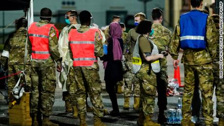 People flown out of Afghanistan leave a transport bus at Ramstein Air Base and are met by soldiers and helpers.