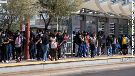 Students wait for the Valley Metro bus to pick them up after their first day at Central High School in Phoenix on August 2, 2021.