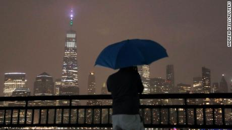 A person with an umbrella stands in falling rain while looking toward New York City ahead of Hurricane Henri in Liberty State Park, Jersey City, New Jersey.