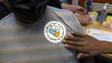 """A healthcare worker puts a sticker on a resident that read in Spanish, """"I got vaccinated against Covid-19"""" after receiving a dose of the Pfizer/BioNTech Covid-19 vaccine at a vaccination site in Lake Worth, Florida, on Friday, Aug. 13, 2021."""