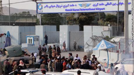 Des combattants talibans montent la garde alors que les Afghans se rassemblent devant l'aéroport international Hamid Karzai pour fuir le pays, à Kaboul, en Afghanistan, le samedi 21 août.