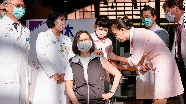 Taiwanese President Tsai Ing-wen, center, receives her first shot of the island's first domestically developed coronavirus vaccine at the Taiwan University Hospital in Taipei, Taiwan on Monday, August 23.