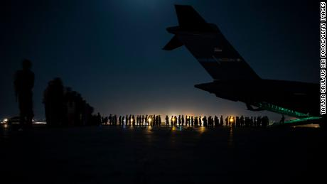 A U.S. Air Force crew prepares to load evacuees onto a C-17 Globemaster III transport aircraft at Hamid Karzai International Airport in Kabul on August 21.
