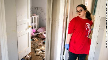 Vanessa Yates checks the damage inside of her home in Waverly following the flood