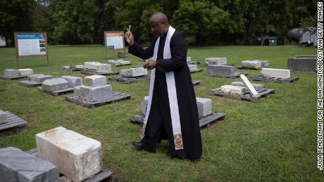 Rev. Lee Gandiya of St. Paul's Episcopal Church blesses gravestones during a ceremonial transfer Monday.