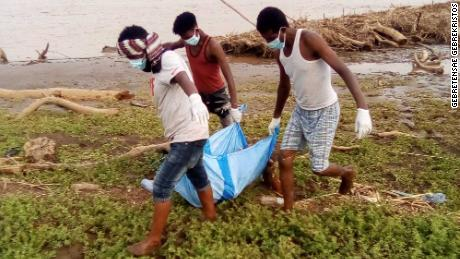A body recovered from the Setit River bank by Wad El Hilou, Sudan, is carried on plastic sheeting.