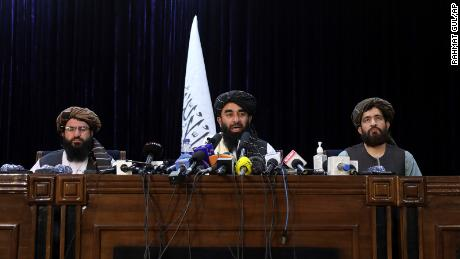 Taliban spokesman Zabihullah Mujahid, center, speaks at his first news conference at the Government Media Information Center, in Kabul, Afghanistan, Tuesday, Aug. 17, 2021.