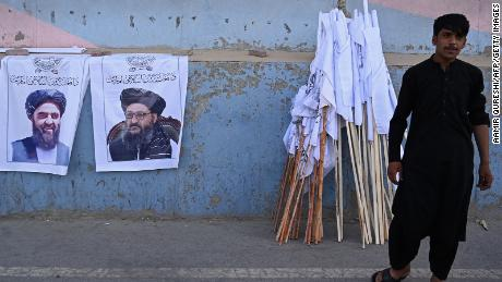 A vendor selling Taliban flags stand next to the posters of Taliban leaders Mullah Abdul Ghani Baradar and Amir Khan Muttaqi as he waits for customers along a street in Kabul on August 27.