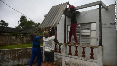 Men place a corrugated metal sheet on the roof of a house under the rain in Batabano, Mayabeque province, about 60 km south of Havana, on August 27, 2021, as Hurricane Ida passes through eastern Cuba.