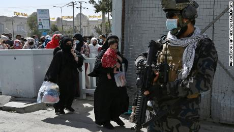 """Taliban Badri fighters, a """"special forces"""" unit, stand guard as Afghans walk through the main entrance gate of Kabul airport on Saturday."""