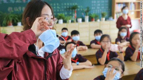 """A primary school teacher shows her students how to properly wear a mask in Lianyungang city, eastern China's Jiangsu Province, on August 30, ahead of the official start of the new semester on September 1. On Friday, China's health authorities announced that the country's Delta variant outbreak has been """"effectively brought under control."""""""