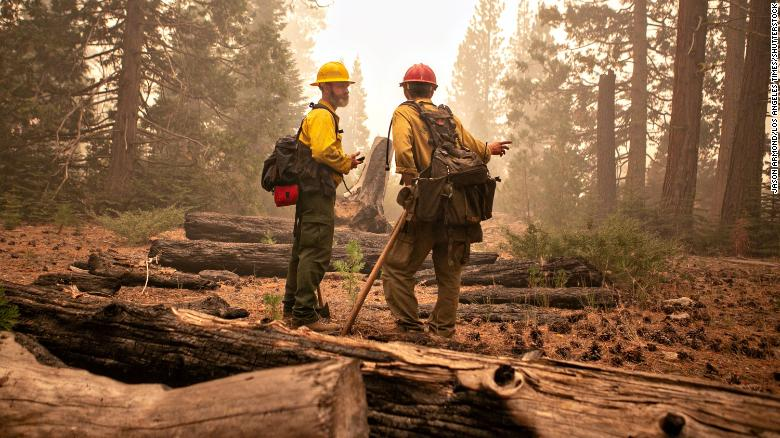 Firefighters with the Eldorado National Forest address the Caldor Fire in Strawberry, California, on Friday, August 27. The raging fire has prompted evacuation orders and warnings in the Lake Tahoe Basin.