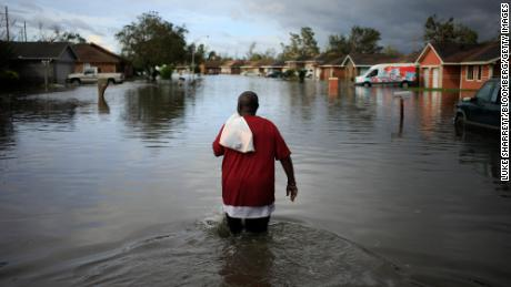 A resident walks through floodwater left behind by Hurricane Ida in LaPlace, Louisiana, U.S., on Monday, Aug. 30, 2021.  The storm, wielding some of the most powerful winds ever to hit the state, drove a wall of water inland when it thundered ashore Sunday as a Category 4 hurricane and reversed the course of part of the Mississippi River. Photographer: Luke Sharrett/Bloomberg via Getty Images