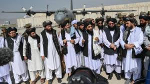 TOPSHOT - Taliban spokesman Zabihullah Mujahid (C, with shawl) speaks to the media at the airport in Kabul on August 31, 2021. - The Taliban joyously fired guns into the air and offered words of reconciliation on August 31, as they celebrated defeating the United States and returning to power after two decades of war that devastated Afghanistan. (Photo by WAKIL KOHSAR / AFP) (Photo by WAKIL KOHSAR/AFP via Getty Images)
