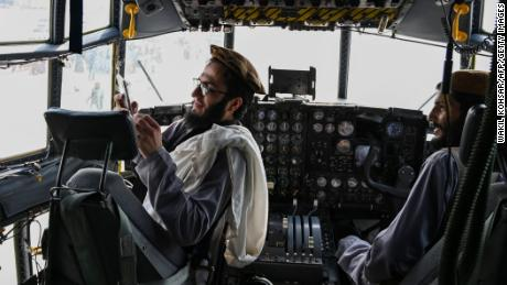 Taliban fighters sit in the cockpit of an Afghan Air Force aircraft at Kabul airport.