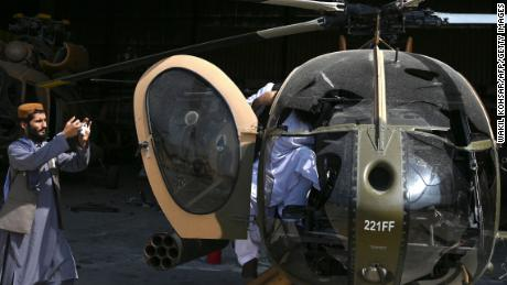 A Taliban fighter takes a photo of a damaged Afghan Air Force helicopter near an airport hangar.