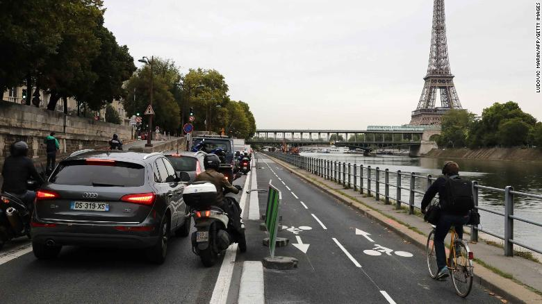 A cyclists rides by congested traffic along the Seine River in Paris.
