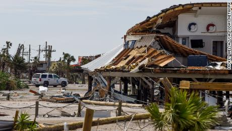 A Louisiana State Trooper keeps watch over damaged homes on Grand Isle on Tuesday.