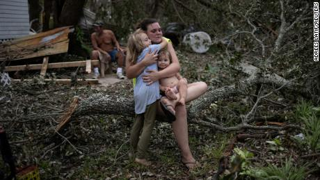 Tiffany Miller is embraced by her daughter Desilynn, 6, as she holds her one year old godchild Charleigh, after the family returned to their destroyed home in the aftermath of Hurricane Ida in Golden Meadow, Louisiana, U.S., September 1, 2021. REUTERS/Adrees Latif     TPX IMAGES OF THE DAY