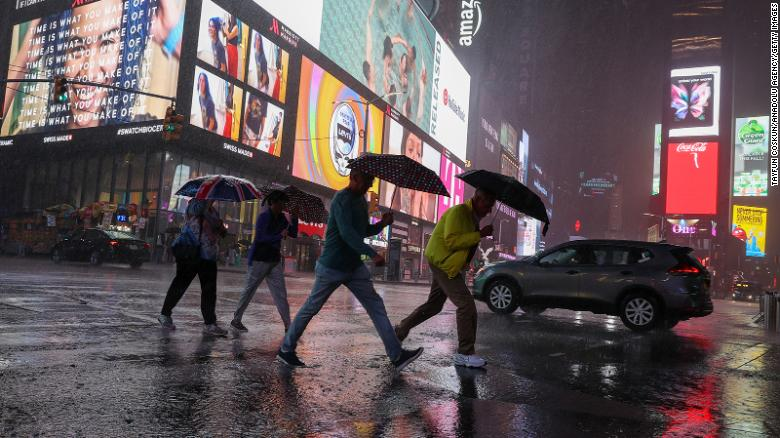 People walk through heavy rain in New York's Times Square on September 1.