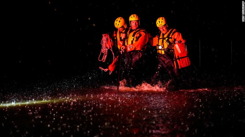 Members of the Weldon Fire Company walk through floodwaters in Dresher, Pennsylvania, on September 1.