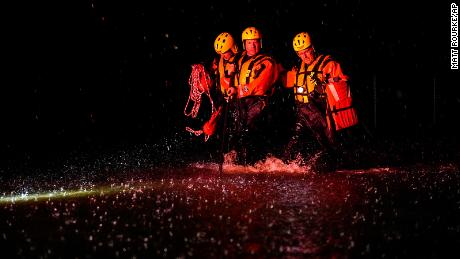 Members of the Weldon Fire Company walk through floodwaters in Dresher, Pennsylvania.
