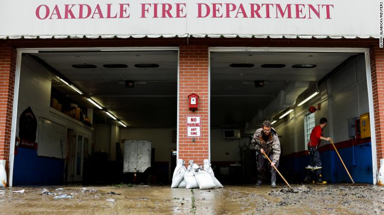 Members of the Oakdale Fire Department clear debris from their station after heavy rains in Oakdale, Pennsylvania, on September 1.