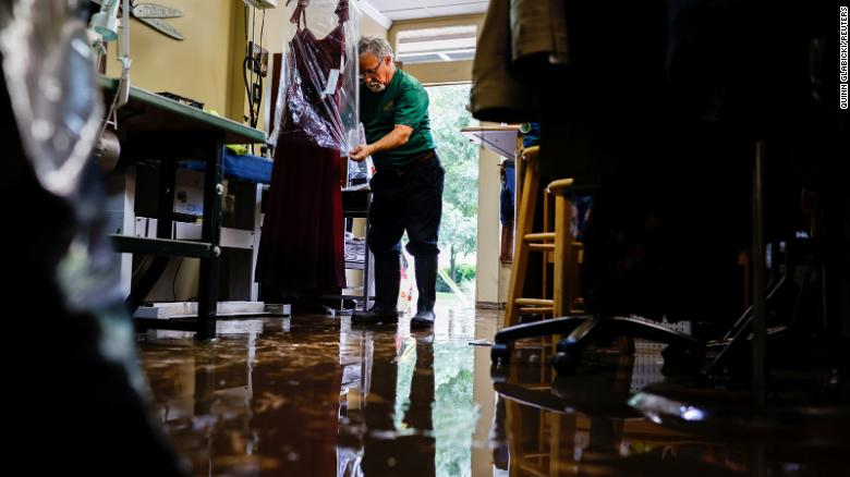 Sergio Rossi, owner of Sergio Tailoring, covers flood-damaged clothing at his shop in Oakdale, Pennsylvania, on September 1.