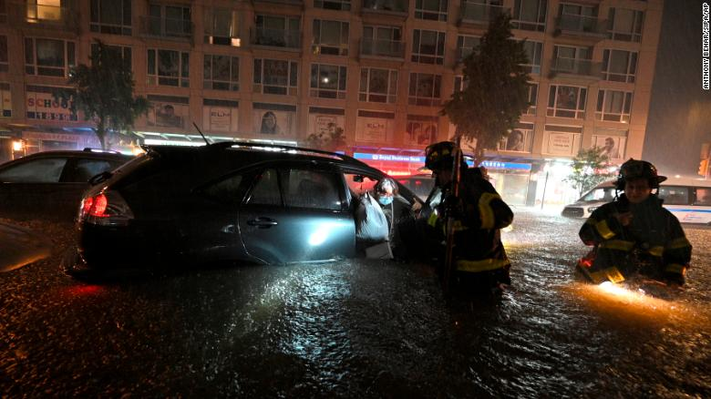 Members of the New York City Fire Department rescue a woman from her stalled car on September 1.
