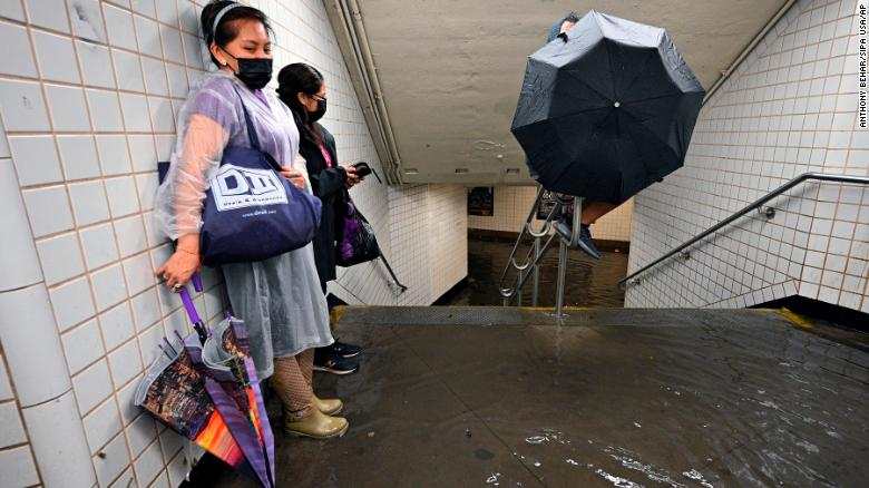 On 1 September 2021 two NYC subway passengers stand against a station wall as flood waters flow past their feet | photo credit CNN dot com