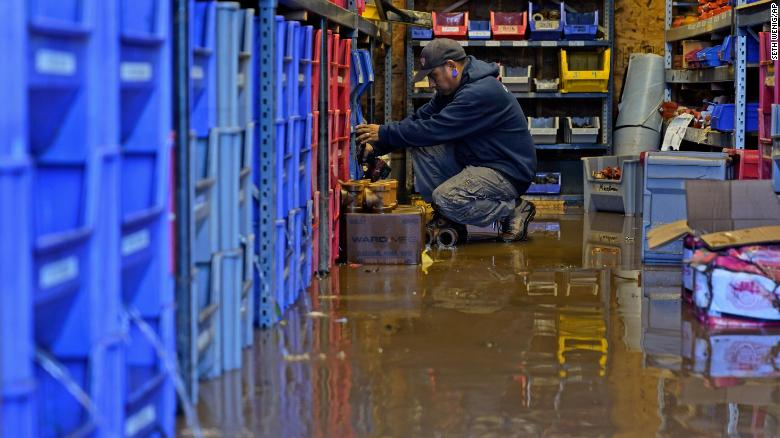 A United Automatic Fire Sprinkler employee helps clean up on September 2 after the business flooded in Woodland Park, New Jersey.