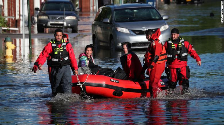 First responders pull local residents in a boat in Mamaroneck, New York, on Thursday.