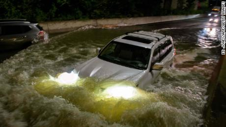 A motorist drives a car through a flooded expressway in Brooklyn, New York.