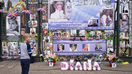 People view tributes left at the gates of Kensington Palace in London on the 24th anniversary of the death of Diana, Princess of Wales.