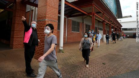8월 27일 호주 시드니의 Qudos Bank Arena NSW 건강 예방 접종 센터에 도착한 사람들을 직원이 안내하고 있습니다.