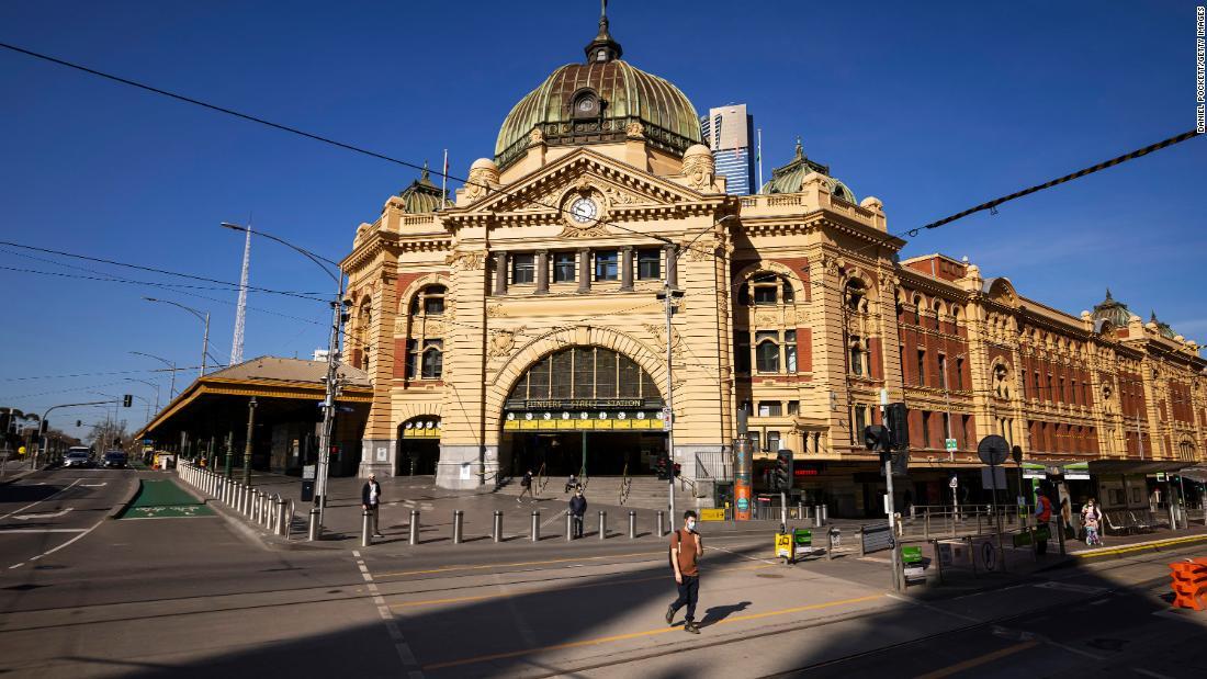 People are seen crossing a quiet Flinders Street on September 1, 2021 in Melbourne, Australia.