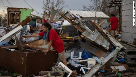 Twin sisters Bridget and Rosalie Cherni, 66, are searching for personal belongings stored in a destroyed barn in Golden Meadow, Louisiana, on Wednesday.