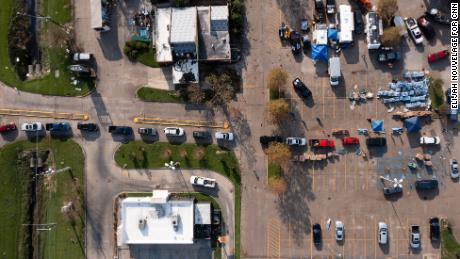 A line of cars waits to receive donated water, toilet paper and other supplies at a giveaway site staffed by volunteers.