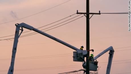 Workers repair damaged power lines in LaPlace. Residents without electricity have sat outside late into the night to try to stay cool.