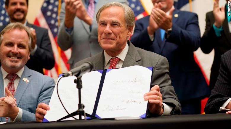 Texas Gov. Greg Abbott shows off Senate Bill 1, also known as the election integrity bill, after he signed it into law on Sept. 7, 2021.