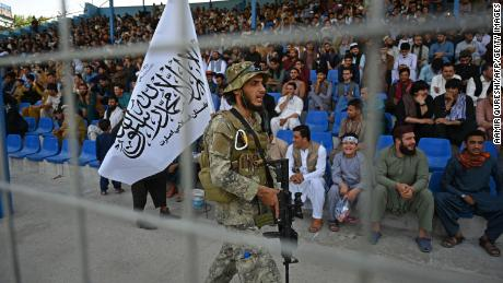 A Taliban fighter stands guard as spectators watch the Twenty20.  to look cricket process match played between two Afghan teams Peace Defenders and Peace Heroes in the Kabul International Cricket Stadium in Kabul on Sept 3, 2021.