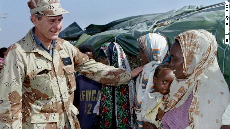 Next, US President George W. Bush greets Somali women during a visit to US troops in Somalia in January 1993.