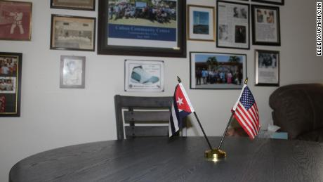 Inside the Cuban Community Center at US Naval Station Guantánamo Bay. The main room includes a wall of photos from the Cuban community. The small table in the room has both an American and Cuban flag displayed on it.