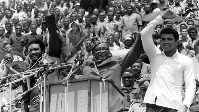 """Zaire's President Mobutu Sese Seko (center) holds George Foreman (left) and Ali's arms aloft in Kinshaha on September 22, 1974 ahead of the fight dubbed """"The Rumble in the Jungle."""""""