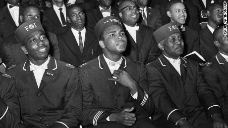 Muhammad Ali listens to Elijah Muhammad as he speaks to other black Muslims in Chicago.