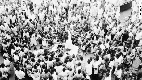 People swarm round world heavyweight boxing champion Muhammad Ali as he sits atop his car during the drive to his hotel after arriving at the airport in Lagos, Nigeria, on June 1, 1964.