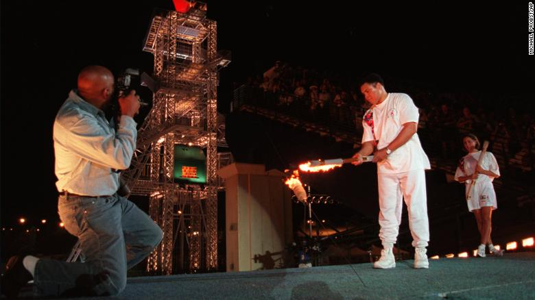 Muhammad Ali uses the Olympic torch to ignite the Olympic flame as swimmer Janet Evans, right, watches during the opening ceremony of the 1996 Summer Olympic Games in Atlanta, on July 19, 1996.