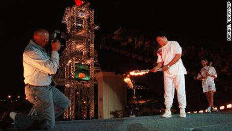 Muhammad Ali uses the Olympic torch to ignite the Olympic flame as Janet Evans, right, watches during the opening ceremony of the 1996 Summer Olympic Games in Atlanta, on July 19, 1996.