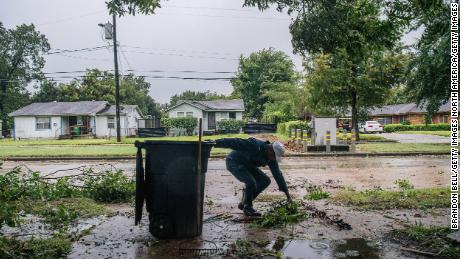 Dallas Baines of Houston throws fallen tree branches into the trash.