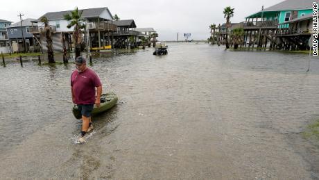 Bubba Ferguson drags a kayak through a flooded street in San Luis Pass, Texas.